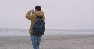 Junger Kerltourist kam auf dem großen Strand mit Seeansicht an, ist- er vom Platz sehr freudig erregt und macht Fotos mit seinem stock footage