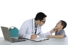 Junger Kinderarzt überprüft Zunge seines Patienten Stockbilder