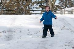Junger kleiner Junge, der das Rodeln draußen an einem Schneetag genießt Stockfotografie