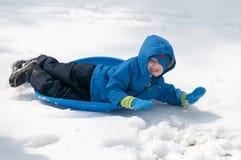 Junger kleiner Junge, der das Rodeln draußen an einem Schneetag genießt Stockbild