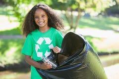 Junger Klimaaktivist, der an der Kamera aufhebt Abfall lächelt Lizenzfreies Stockfoto