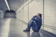 Junger kranker Mann verlor die leidende Krise, die auf Boden Straßen-U-Bahntunnel sitzt