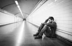 Junger kranker Mann verlor die leidende Krise, die auf Boden Straßen-U-Bahntunnel sitzt Stockbilder