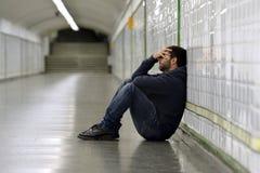 Junger kranker Mann verlor die leidende Krise, die auf Boden Straßen-U-Bahntunnel sitzt Stockfotos