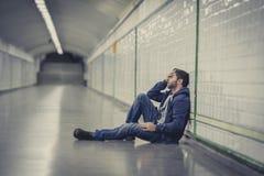 Junger kranker Mann verlor die leidende Krise, die auf Boden Straßen-U-Bahntunnel sitzt Lizenzfreie Stockfotos