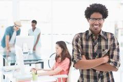 Junger kreativer Mann, der an der Kamera lächelt Stockbilder