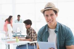 Junger kreativer Mann, der seine Tablette verwendet Stockfoto