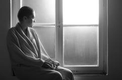 Junger Krebspatient, der auf Krankenhausfenster sitzt Stockbilder