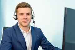 Junger Kundenbetreuungs-Telefon-Betreiber mit Kopfhörer an seinem Arbeitsplatz im Büro lizenzfreie stockfotos
