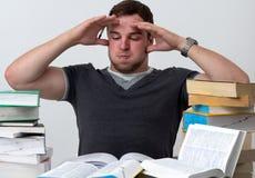 Junger Kursteilnehmer überwältigt mit dem Studieren Lizenzfreie Stockbilder