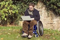 Junger Kursteilnehmer auf einem Rollstuhl am Park Lizenzfreies Stockbild
