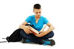 Junger Kursteilnehmer, der ein Buch auf dem Fußboden liest Lizenzfreies Stockbild