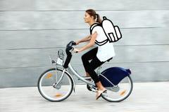 Junger Kursteilnehmer, der zur Universität mit dem Fahrrad fährt Stockbilder
