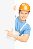 Junger lächelnder Bauarbeiter mit Sturzhelm zeigend auf Platte Lizenzfreie Stockfotografie