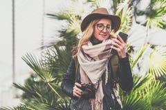 Junger lächelnder Frauentourist im Hut und in Brillen, die im Freien stehen und Smartphone verwenden Mädchen, das auf Schirm des  Stockfoto
