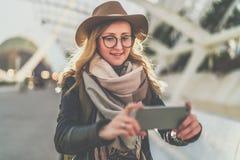 Junger lächelnder Frauentourist im Hut und in Brillen, die im Freien stehen und Smartphone verwenden Mädchen, das auf Schirm des  Lizenzfreies Stockfoto