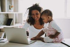 Junger lächelnder Freiberufler mit Tochter zu Hause stockbild