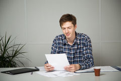 Junger lächelnder Geschäftsmann beim Ablesen eines Berichts an dem Arbeitsplatz Stockfotografie
