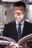 Junger lächelnder Geschäftsmann, der ein Buch liest lizenzfreie stockfotos