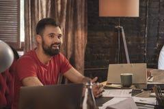 Junger lächelnder Geschäftsmann mit dem Bart, der herein sitzt, beginnen oben dunkles Büro Lizenzfreies Stockbild