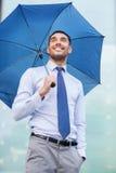 Junger lächelnder Geschäftsmann mit Regenschirm draußen Stockbilder