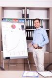 Junger lächelnder Geschäftsmann nahe bei einer Flip-Chart lizenzfreie stockfotografie