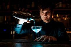 Junger lächelnder Kellner, der neues Getränk mit blauem Alkohol von einem Schüttel-Apparat in ein Glas unter Verwendung des Siebs Lizenzfreies Stockbild