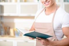 Junger lächelnder Koch liest ein Kochbuch Stockfotografie