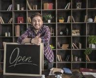 Junger lächelnder lederner Hersteller des Mannes, der nahe offenem Zeichen am Holztisch steht Lizenzfreie Stockbilder