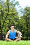 Junger lächelnder männlicher Athlet, der sich auf einem Gras mit Ball herein hinsetzt Stockbild