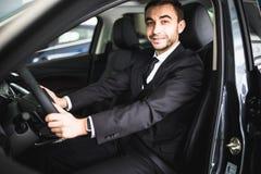Junger lächelnder Mann beim Fahren in sein Auto Stockbild