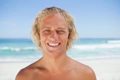 Junger lächelnder Mann, der auf dem Strand steht Stockbilder