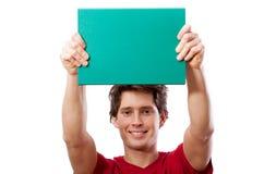 Junger lächelnder Mann, der grünes Brett für Ihren Text hält Stockbild