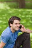 Junger lächelnder Mann, der mit seinem Mobiltelefon beim Sitzen in a nennt Lizenzfreie Stockbilder