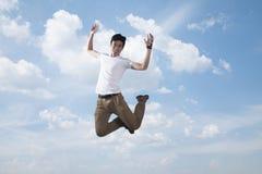 Junger lächelnder Mann, der in mitten- in der Luft, Himmel- und Wolkenhintergrund springt Stockfoto