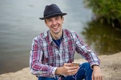 Junger lächelnder Mann in der modernen Kleidung hört Musik Stockfotos
