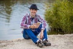 Junger lächelnder Mann in der modernen Kleidung hört Musik Lizenzfreies Stockfoto