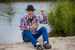 Junger lächelnder Mann in der modernen Kleidung hört Musik Lizenzfreie Stockfotos