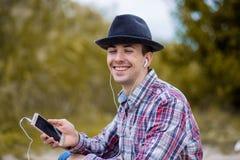 Junger lächelnder Mann in der modernen Kleidung hört Musik Stockfotografie