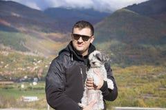 Junger lächelnder Mann, der seinen kleinen weißen Hund im Herbstberg umarmt Stockbild