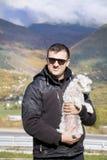 Junger lächelnder Mann, der seinen kleinen weißen Hund im Herbstberg umarmt Lizenzfreies Stockfoto