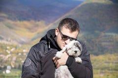 Junger lächelnder Mann, der seinen kleinen weißen Hund im Herbstberg umarmt Lizenzfreie Stockfotos