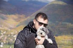 Junger lächelnder Mann, der seinen kleinen weißen Hund im Herbstberg umarmt Lizenzfreies Stockbild