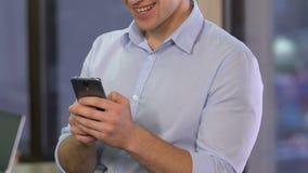 Junger lächelnder Mann, der Smartphone im Büro, plaudernd auf der Datierung von Website in einer Liste verzeichnet stock video footage