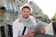 Junger lächelnder Mann mit dem Hut, der heraus in der Stadt hängt Stockfotografie