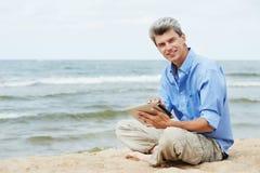 Junger lächelnder Mann mit Tablette-PC auf Küste Lizenzfreie Stockfotografie