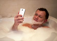 Junger lächelnder Mann sitzt Badezimmer macht Bart nimmt selfie stockfotos