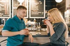 Junger lächelnder Mann und Frau, die zusammen in der Kaffeestube sitzt nahe Barzähler, Paar von den Freunden trinken Tee, Kaffee  lizenzfreie stockbilder
