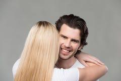 Junger lächelnder Mann, wie er von seiner Frau umarmt wird Stockfoto