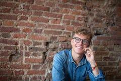 Junger lächelnder Mannmanager, der am Handy mit dem Kollegen, sitzend im modernen Büro gegen Wand mit Kopienraum spricht stockbild